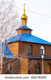 Rural landscape. Small wooden Orthodox Church with a dome, a cross and a blue roof
