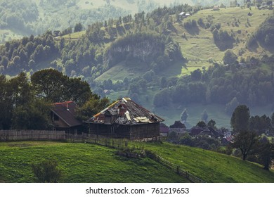 Rural landscape with traditional Romanian wooden houses uphill in Magura village, Brasov county, Romania.