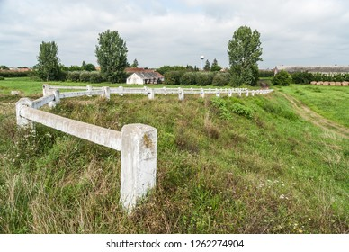 Rural landscape - white painted concrete fence on the embankment