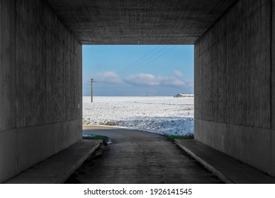 rural landscape at winter time seen from a concrete underpass