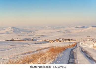 RURAL LANDSCAPE WINTER.Between Apulia and Basilicata. snowy hills landscape with farmhouses. -ITALY- .In the background the mountains of Lucania.