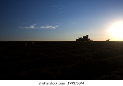Rural machine working at agriculture field at sunset.