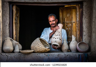 A rural man standing in the net and showing some pottery products in Kom Ombo. South Egypt, August 2015