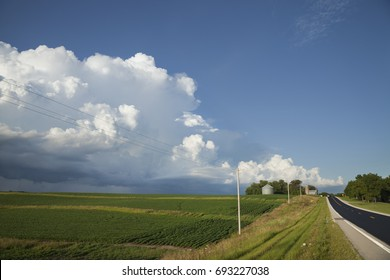 Rural midwest road and fields under big dramatic clouds
