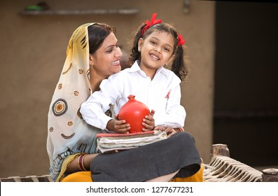 Rural mother with daughter saving money in piggy bank for future education