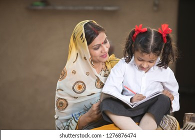 Rural mother helping daughter with her homework