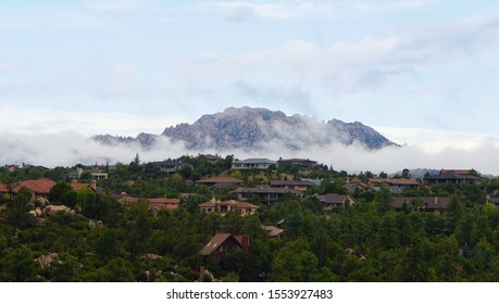 A rural neighborhood sits at the base of  a cloud shrouded mountain in the early morning.