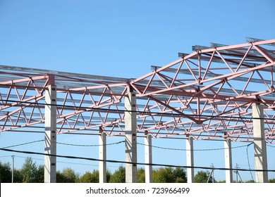 Rural outdoor industrial commercial building framework construction in sunny summer day over blue cloudless sky