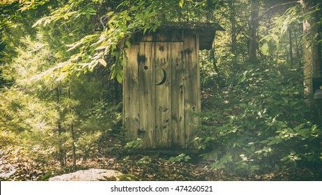 Rural Outhouse. A typical old fashioned outhouse bathroom in a wooded, forest area.