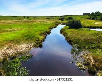 Rural prairie landscape with a boggy creek running through marsh land in summer.