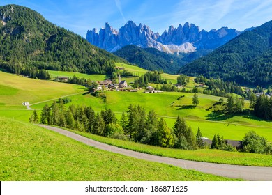 Rural road in green alpine valley with view of Santa Maddalena village church, Val di Funes, Dolomiti Mountains, Italy
