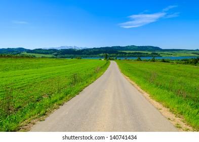 Rural road green pasture Tatry Mountains distant view, Czorsztyn lake, Pieniny Mountains, Poland