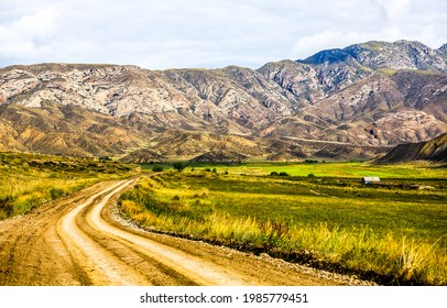 Rural road in mountain valley. Mountain valley road. Road in mountain valley. Mountain valley landscape