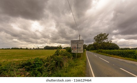 Rural Road in Somerset England, Heavy Clouds Before Rain, Road Direction Sign Cheddar, Wells, Bath and Radstock, summer 2018