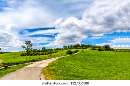 Rural road under cloudy sky landscape. Rural road cloudy sky. Country road landscape. Hill road rural scene