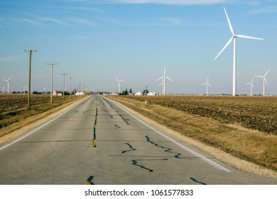 Rural road with wind farms and traditional farms on either side in spring, northern Illinois, USA, for travel, agricultural, or industrial themes