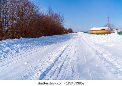 Rural road in winter covered with rolled snow on the background of snow-covered fields and forests with a clear blue sky