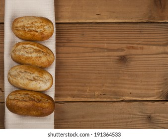 Rural scene with bread and white textile on wooden background. Copy space.