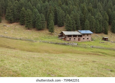 Rural scene from a refuge with photovoltaic panels among a mountain pasture in Val di Funes, Italy
