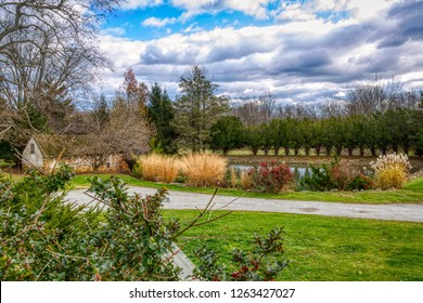 Rural scene of a spring house alongside a pond surrounded evergreens, reeds and decorative bushes with red berry laden holly bushes in the foreground.  Chester County, Pennsylvania