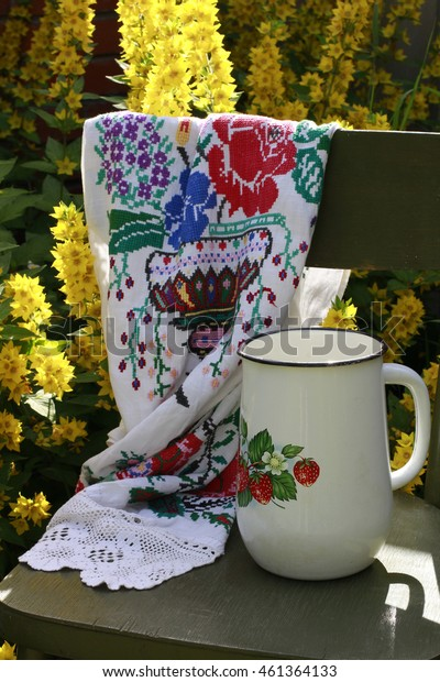 Rural scene: vintage original wooden Vienna chair, handmade embroidered linen towel with lace and old white enamelled jug, high angle view, vertical picture