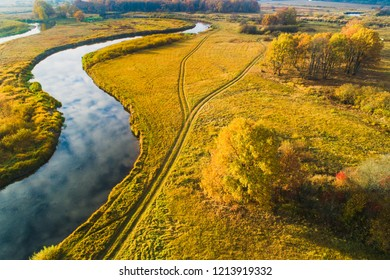 Rural scenery. Meadow with river from above. Meadow with autumn colors on a sunny day. Fall background. Rural scenery.
