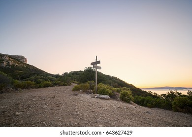 Rural scenic landscape with crossroad on hill in forest at sunset. Two different directions. Concept of choose the correct way. Right and left path. Junction, fork, split road.