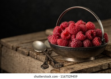 Rural still life with raspberries on rustic  table. fresh juicy berries over old wooden background