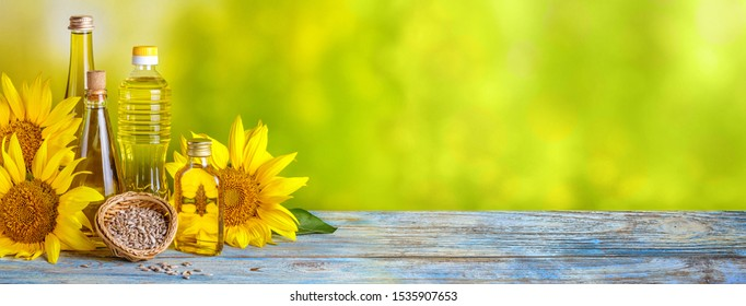 Rural still-life, banner - sunflower oil in bottles with flowers of sunflower (Helianthus annuus), closeup with space for text