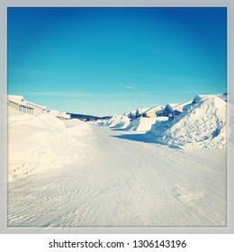 Rural Street in Labrador, Canada with huge piles of snow