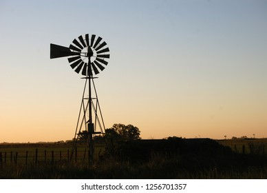 Rural sunset landscape in the countryside of Argentina with a mill to extract water