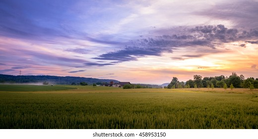 Rural Sunset Landscape of Swiss Farmland With Tractor And Farm-House In Background