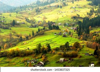 rural ukrainian landscape, colorful autumn scenery with  huzul village on the slope of mountain, wooden houses and multicolor trees, Ukraine, Europe, Carpathians, famous Jasinja village near Rahov