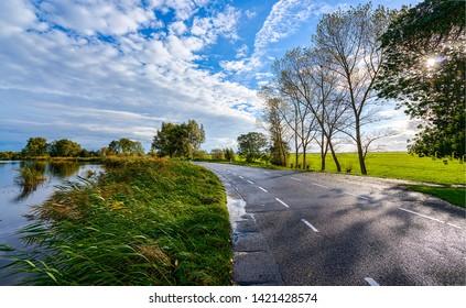 Rural village road sunset sky clouds landscape. Evening rural road view. Dusk country road sky clouds. Rural country road in evening