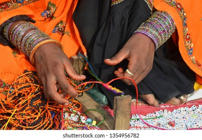 a rural village women making bands with different colorful threads in a stadium fair