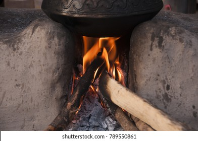 Rural vintage kitchen using firewood in earthen chulhas for cooking food.