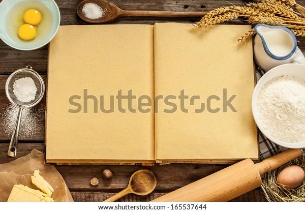 調理用の本を空にし、ケーキの具材(卵、小麦粉、牛乳、バター、砂糖)や調理器具を使った、田舎のビンテージウッドのキッチンテーブル。国の背景と無料のレシピテキストスペース。