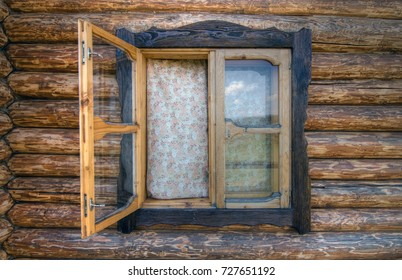Rural window of a wooden cottage with curtains