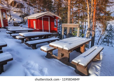 Rural winter landscape with generic red wooden cottage and outdoor furniture under snow, Finland