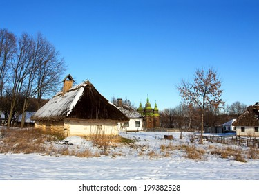Rural winter landscape with the view of rustic wooden log huts with a straw roof in a sunny frost day