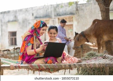 Rural woman using laptop with her daughter.