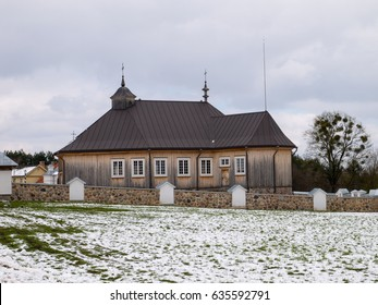 Rural wooden church against grass and snow meadow