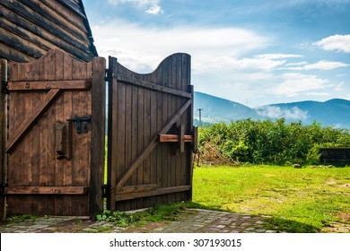 Rural wooden gate and green lawn with grass, mountains, blue sky