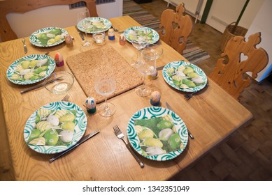 Rural wooden table decorated for the Easter meal with traditional ceramics, wine glasses, Easter eggs and festive napkins.