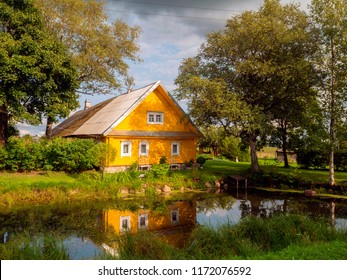 Rural yellow house mirroring in water framed by trees