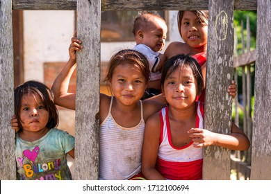 Rurrenabaque, Beni / Bolivia - May 11 2016: Young and Little Indigenous Amazonian Girls Smiling Between Plank Fence