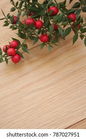 Ruscus aculeatus, known as butcher's-broom. Branch with red berries and green leaves on wooden table