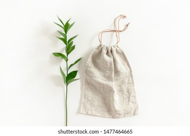 Ruscus branch and canvas bag on white background