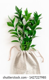 Ruscus branches in canvas bag on white background