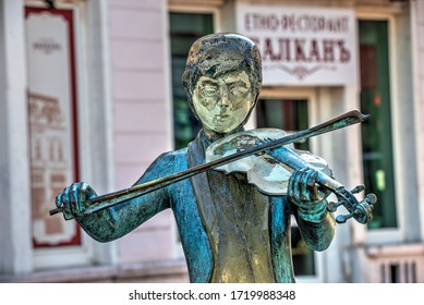 Ruse, Bulgaria - 07.26.2019. Sculpture of a violinist boy in the city of Ruse in Bulgaria, on a sunny summer day